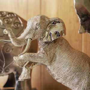 Hopeanvärinen takajaloilla seisova norsu-koristepatsas hyllyllä.