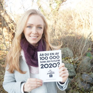 """Maja Rosén håller upp kampanjskylten """"Är du en av 100 000 som är flygfri 2020?"""""""