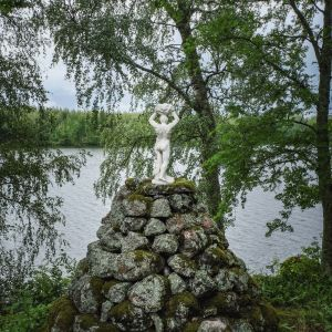 Valkoinen pieni miespatsas selin kameraan kiviröykkiön päällä, taustalla järvimaisemaa