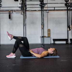 Tränaren Jonna ligger på rygg på en träningsmatta med knäna böjda och det ena benet lutar på det andra knäet.