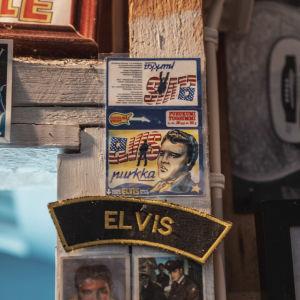 """Paperilappu jossa Elvis Presleyn kuva sekä teksti """"Elvis-purkka"""" kiinnitettynä ovenpieleen."""
