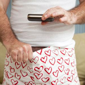 En bild av en man som fotar ner i sina boxershorts, med en mobiltelefon.