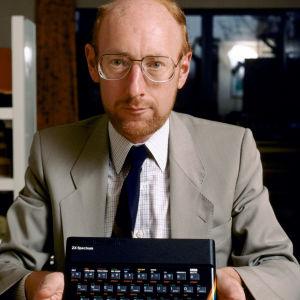 Clive Sinclair pitää kädessään Sinclair ZX Spectrum -mikrotietokonetta.