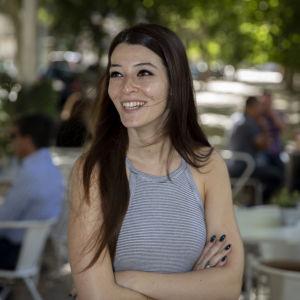 Maria Luis Duro, en ung kvinna med långt mörkt hår står i en lummig park i Lissabon.
