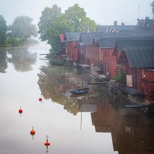 Röda strandbodar och en båt vid en dimmig åstrand