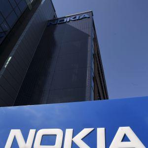 Stor skylt med namnet Nokia i Bakgrunden kontorsbyggnader och blå himmel och ett moln fotograferade nedifrån. Nokias huvudkontor i Esbo.