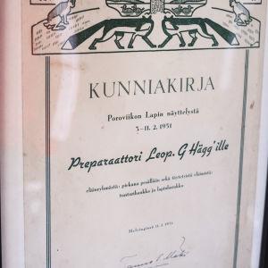 """Diplom med texten """"Kunniakirja Poroviikon Lapin näyttelystä 5.-11.2.1951 Leopold g. Hägg'ille eläinryhmästä: piekana pesällään sekä täytetyistä eläimistä: tunturihaukka ja lapinharakka."""""""