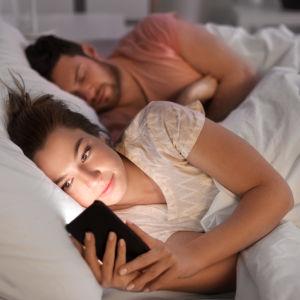 Kvinna ligger och tittar på telefonen medan mannen bakom henne sover.