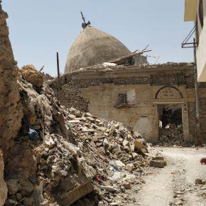 En moské ligger i ruiner, omgiven av bråte orsakat av krigföring.