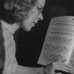 Nuori nainen pianon ääressä tapailee koskettimilla nuotteja