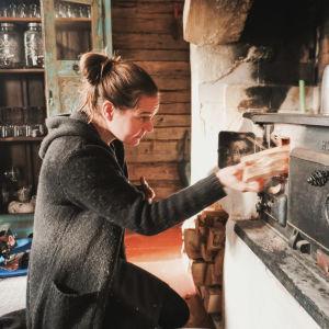 Nainen laittaa halkoa vanhaan uuniin.