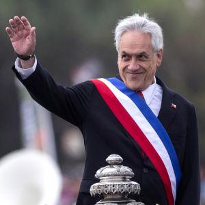 Chiles president ler och ser åt sidan. Hans hand är utsträckt eftersom han hälsar.