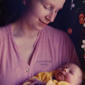 Nuori äiti ja tyttö-vauva Kätilöopiston vaatteissa