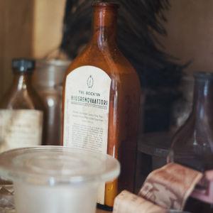 Brun flaska med gammal etikett: Tri Bockin hiusrenovaattori.