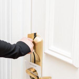 En man använder ett nyckelkort för att låsa upp en hotelldörr.