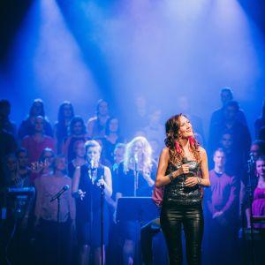 Här står Elna Romberg på scenen under en konsert på Svenska Teatern.