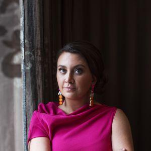 Camilla Läckberg vid ett fönster, iklädd mörkrosa skjorta.