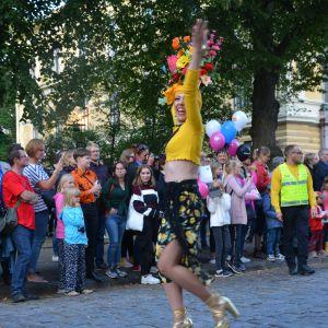 Kvinna i färgglada kläder dansar på gatan.
