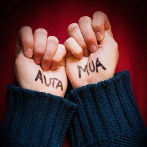 kaksi kättä nyrkissä, joihin on kirjoitettu: auta mua