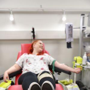 nuori nainen makaa verenluovutuksessa punaisella tuolilla