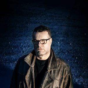 Mikael Crawfords ser allvarlig ut och står tittandes in i kameran mot en mörk bakgrund.
