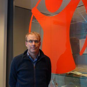 Foto på Max Holm som poserar intill Rädda Barnens röda logotyp