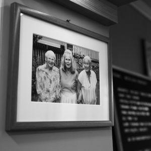 Svartvitt foto av Nick Victorzons mamma, mammas faster och mormor på restaurangväggen.