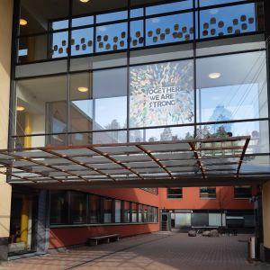 Granhultsskolans byggnad i glas och betong med texten Together we are strong skriven av elever på ett av fönstren.