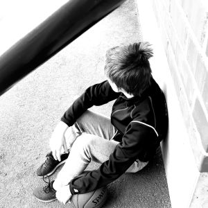 Pojke sitter med bortvänt ansikte utomhus och hans hand vilar på en basketboll.