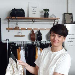 Ägare Jonna Raikamo håller upp klädesplagg i sin klädaffär.