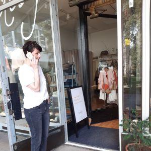 Egenföretagare Jonna Raikamo talar i sin mobiltelefon i dörröppningen till sin klädaffär.
