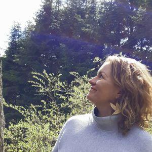 Johanna Sandberg står i profil och tittar uppåt mot träd och himmel.