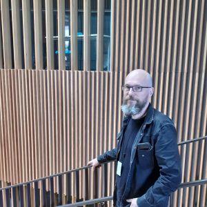 Rasmus Vuori står mörkklädd och håller i en ledstång mot en vägg av spjälverk i trä i aulan till Aalto-universitetet.