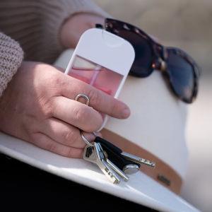 Avainnippu, käsidesi, aurinkolasit ja hattu Veera Biancan kädessä.