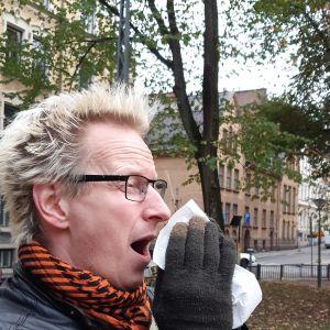 Närbild på Jonas Francks ansikte när han nyser och för en vit näsduk mot ansiktet.