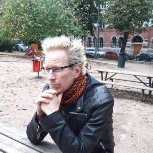 Jonas Franck sitter med hakan i händerna vid ett bord i en park och tittar rakt fram.