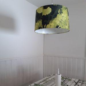 Köksbord med duk i grönt och vitt som föreställer björkstammar, vit panelad vägg bakom köksbordet och en taklampa med grön skärm.