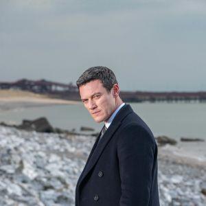 Luke Evans katsoo kameraan seisoen rannalla.