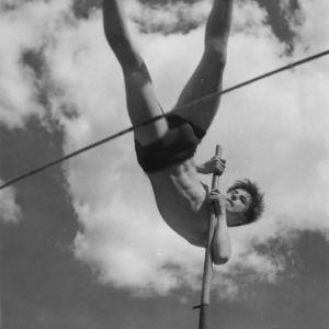 Nuori mies, Jussi Huttunen, hyppää seivästä 1950-luvulla.