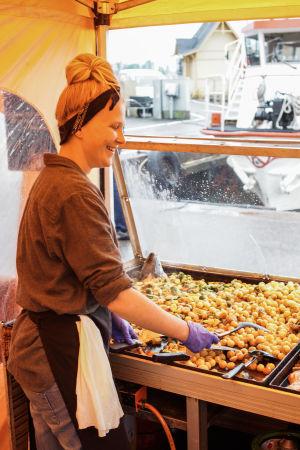 Mikaela Heikiö steker grönsaker i ett gatukök på Salutorget.