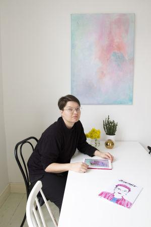 Zarah Holmberg sitter vid ett bord och ritar med sin ipad. På bordet ligger också tidningen hon gjort.