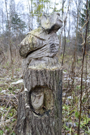 en uggla och en uggleunge har skulpterats i en stubbe med motorsåg