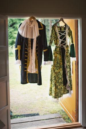 Två dräkter som används i en operapjäs är upphängda i en dörröppning.