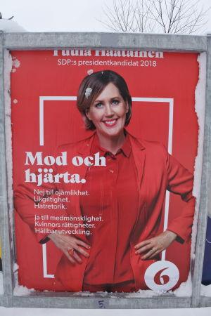 tuula haatainens valaffisch. hon har röda kläder och står mot en röd bakgrund.