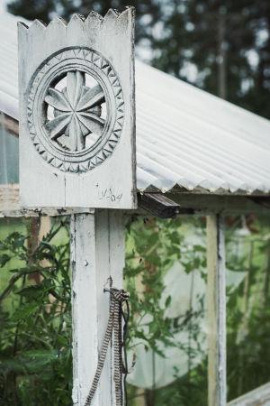 Kasvihuone jonka nurkalla puuveistosyksityiskohtia.