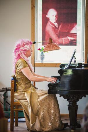 Pianisti Sonja Hendunen soittaa flyygeliä, päällä kullanvärinen iltapuku, päässä pinkki peruukki