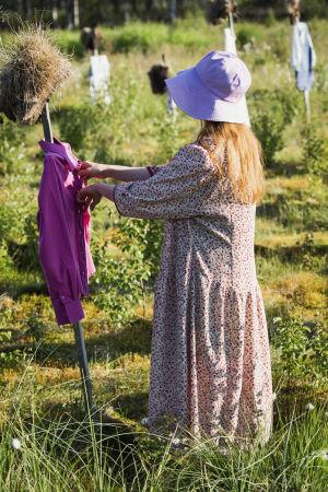 Nainen violetti hellehattu päässä (kasvot eivät näy) ja punainen pitkä kukkamekko päällä avaamassa violetinväristä pusakkaa Hiljaisen kansan heinäpäisen hahmon päällä.