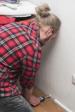 Jesse-Pekka Rautiainen, som bor i ett hus med inomhusluftproblem i Marudd i Helsingfors, mäter fuktighetshalter vid ett ställe där de saknas golvlist, i ett rum med en klar mikroblukt.