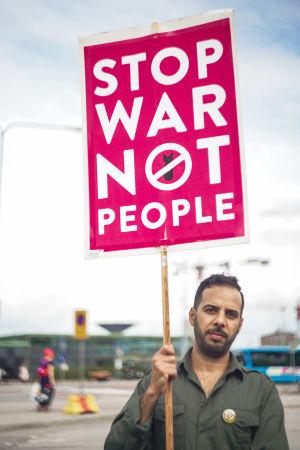 """Saad Ali står på ett torg vid Hertonäs metrostation. Han har en skylt i handen, som det står """"Stop war not people"""" på."""