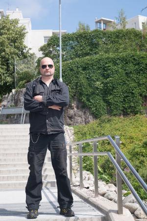 Mellungsbackabon Sebastian står på trapporna på Bredbergstorget. Han är klädd i svarta kläder, med svarta solglasögon och ser bestämd ut.